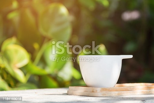 853676006 istock photo Coffee cup on wooden table in garden with bright green background; copy space 1184169018