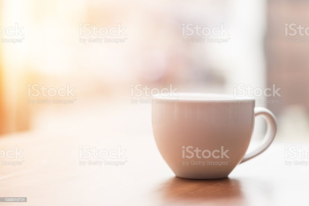 Coffee cup on wooden table in the morning with gold light feeling warm,Selective focus