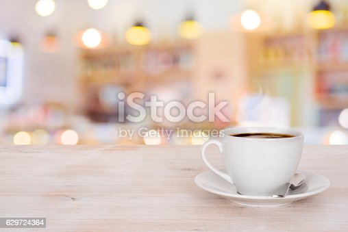 istock Coffee cup on wooden table over defocused cafeteria background 629724364