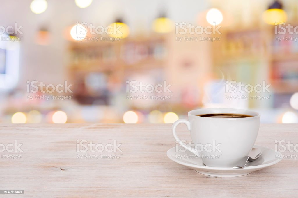 Coffee cup on wooden table over defocused cafeteria background stock photo
