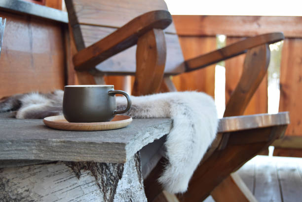 Coffee cup outside on mountain lodge porch Dark green coffee cup outside on mountain lodge porch with reindeer skins and chair. chalet stock pictures, royalty-free photos & images