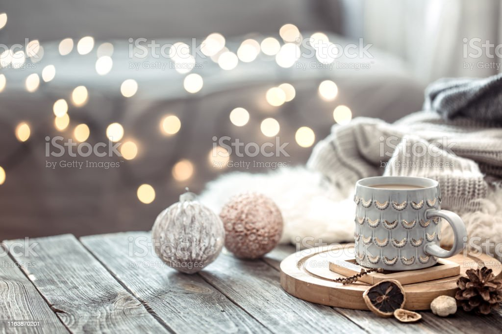 Coffee cup over Christmas lights bokeh in home on wooden table with...