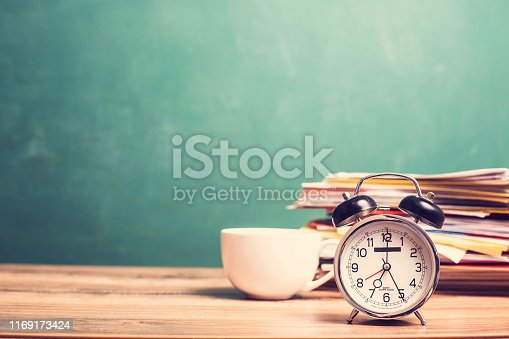 Back to school. Coffee cup on teacher's desk with stack of student papers and alarm clock in front of green chalkboard.  Classroom setting.