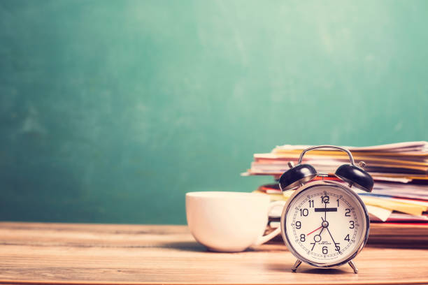 Coffee cup, papers stack, alarm clock on wooden school desk with chalkboard. stock photo