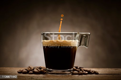 Black coffee in glass cup with coffee beans and jumping drop, on wooden table