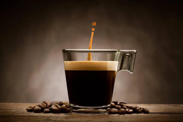coffee cup Black coffee in glass cup with coffee beans and jumping drop, on wooden table caffeine stock pictures, royalty-free photos & images
