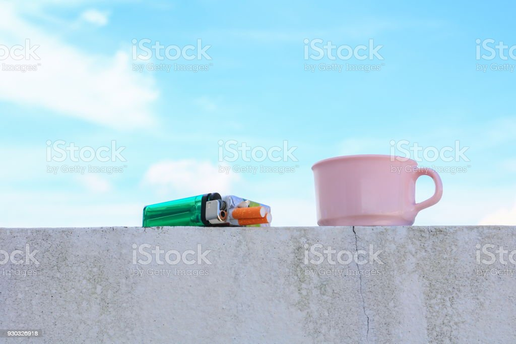 coffee cup pink and a cigarette pack lighter on the floor. with  blue sky background concept Non-smoking day universal stock photo