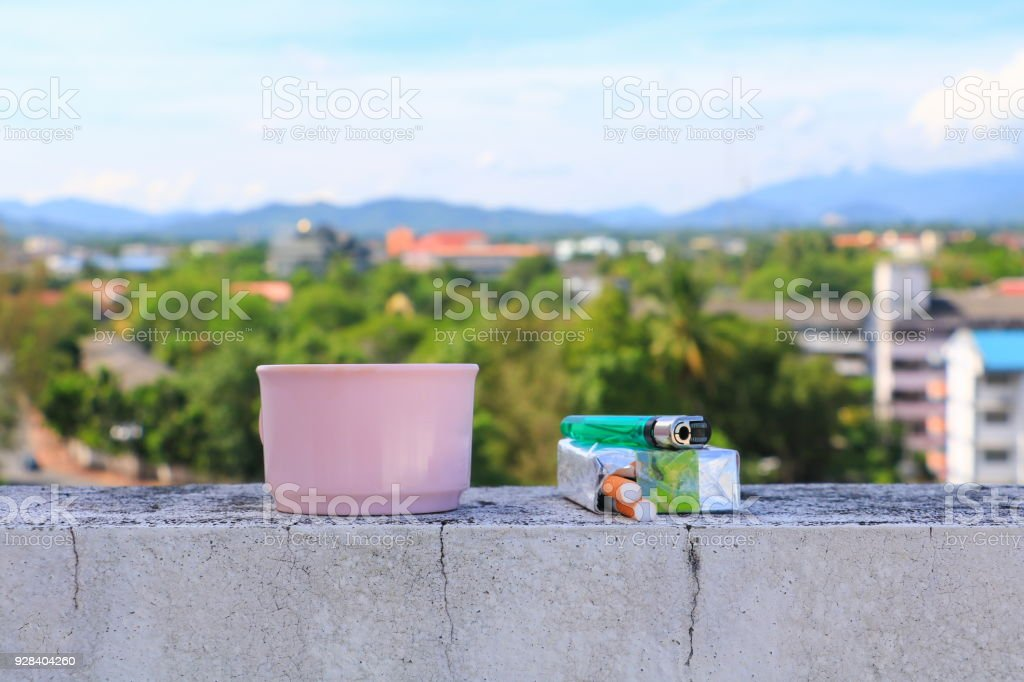 coffee cup pink and a cigarette pack lighter on the floor. with city blue sky background concept Non-smoking day universal stock photo