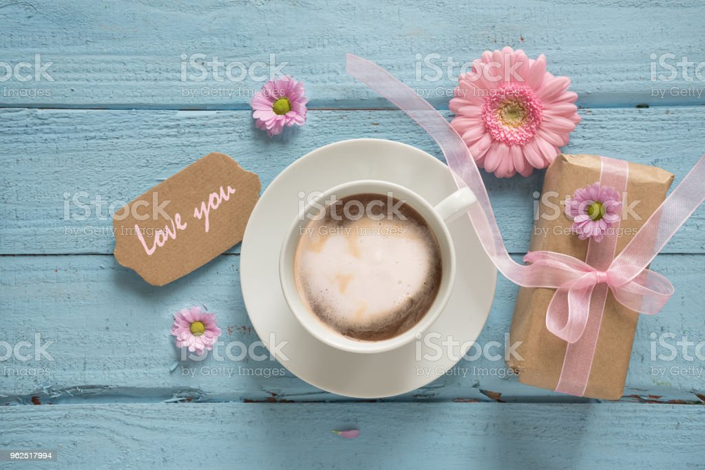 Coffee cup, pink flowers and a gift on pastel blue wood background with copy space, text Love you, top view from above - Royalty-free Above Stock Photo