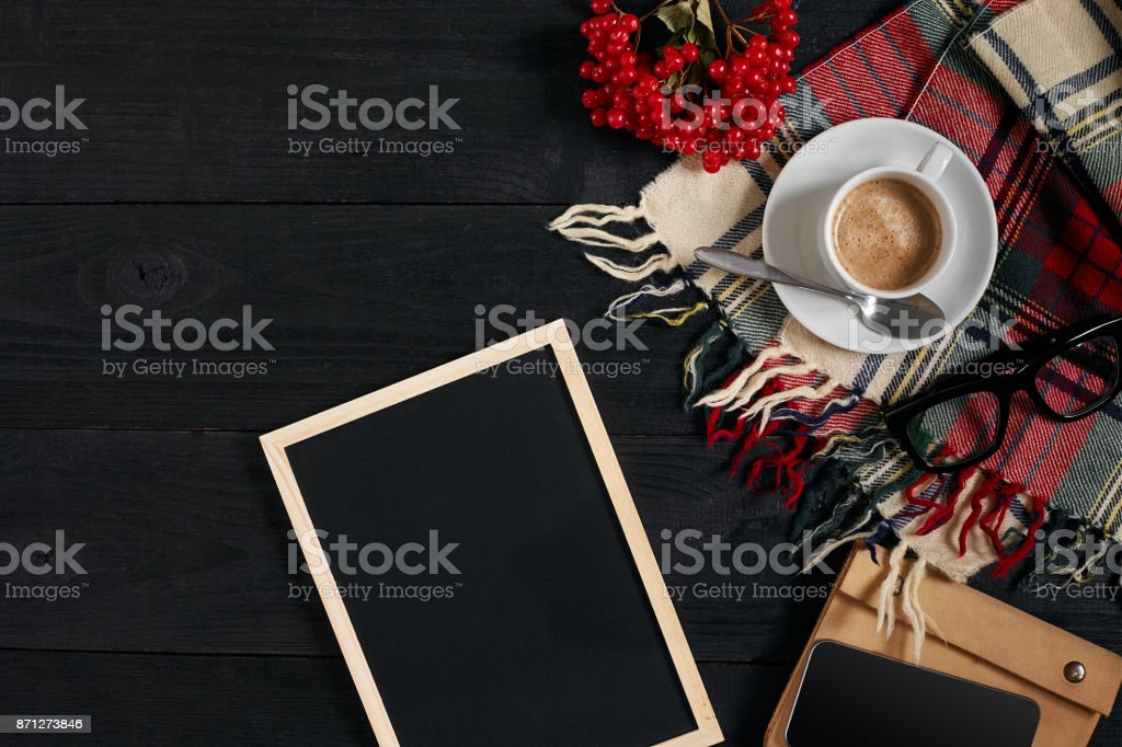 Coffee cup, scarf in a cage, notebook and phone on wooden table. Top view with chalkboard for your text stock photo