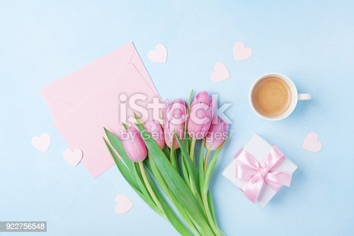 istock Coffee cup, spring tulip flowers, gift box and pink paper card on blue pastel table top view. Greeting for Womans or Mothers Day. 922756548