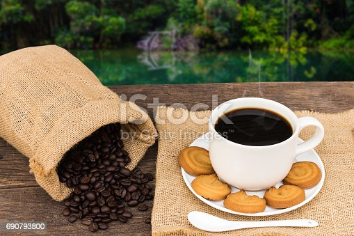 1135319558 istock photo Coffee cup with burlap on the wooden table and forest and river background 690793800