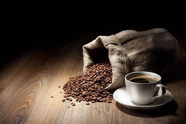 Kaffeetasse mit Jute sack von gerösteten Bohnen auf rustikalen – Foto