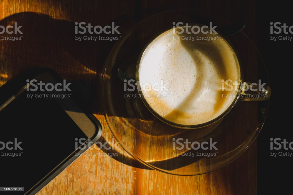 Coffee cup with cell phone on coffee table stock photo
