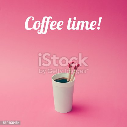 istock Coffee cup with female doll legs on pink background. Coffee concept. 672406454