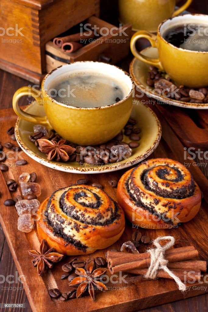 Baked sweet buns with vanilla and coffee on wood table