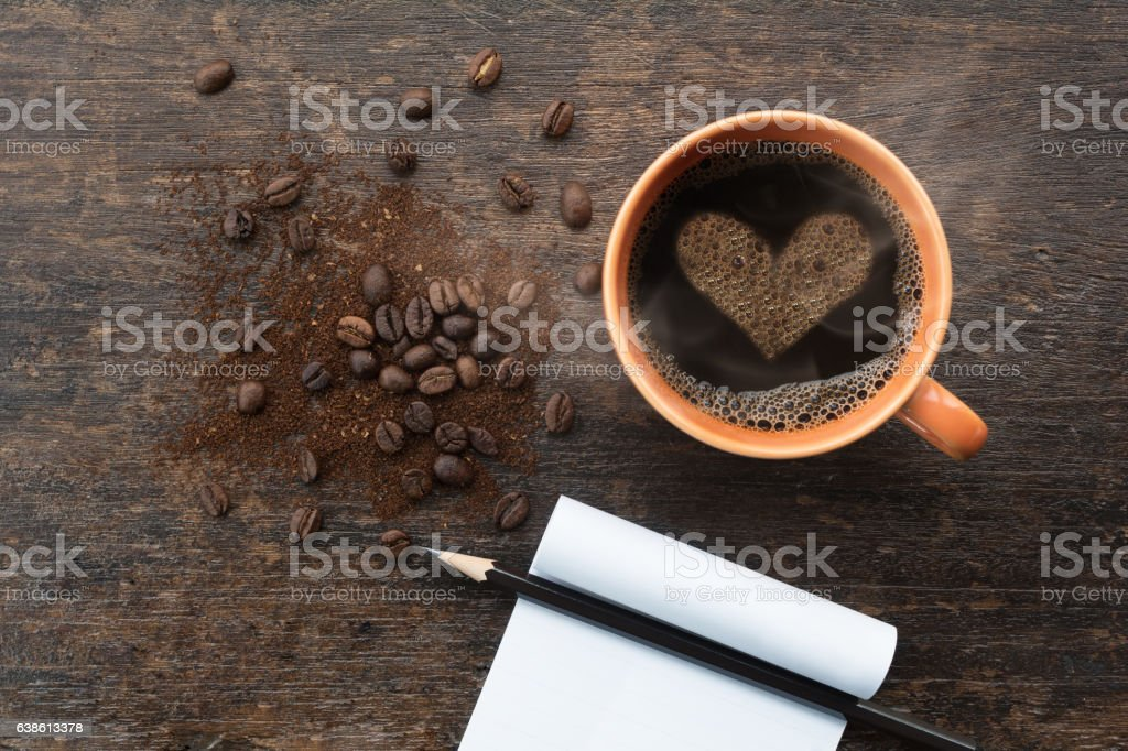 Coffee cup with heart shape crema and coffee beans - foto de stock