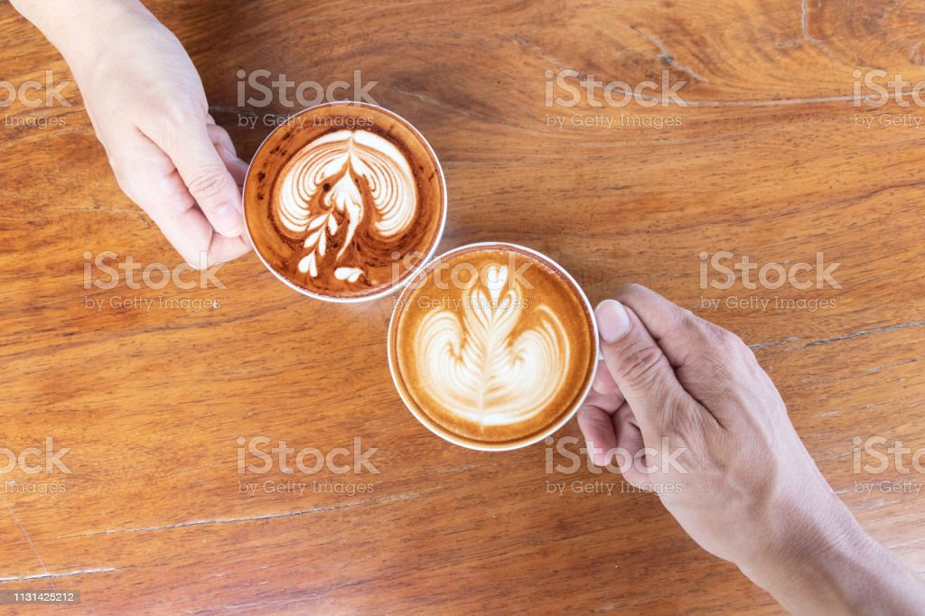 Coffee cup with latte art foam on wood table in coffee shop with copy...