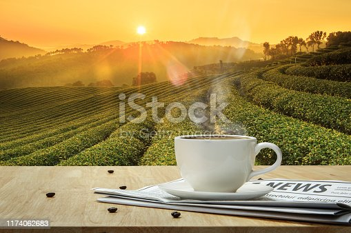 Coffee cup with newspaper on the wooden table and the Plantations background