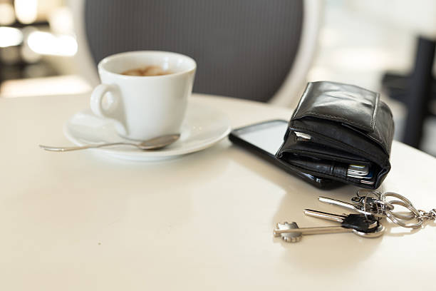 Coffee cup with phone and leather wallet on table stock photo