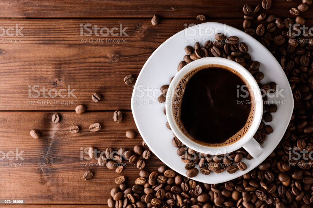 Coffee cup with saucer and beans on wooden table. stock photo