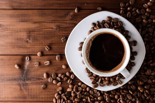 kaffeetasse mit untertasse und bohnen auf holztisch. - wärmeplatte stock-fotos und bilder