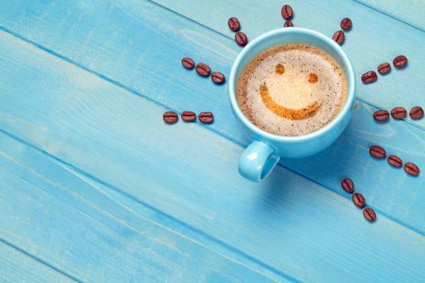 kaffeetasse mit smiley-gesicht auf blauen holztisch - gesichtertassen stock-fotos und bilder