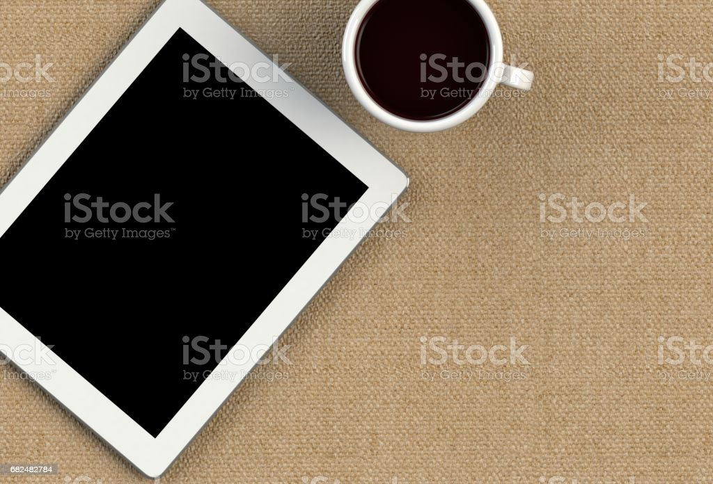 Coffee cup with tablet on brown fabric table Стоковые фото Стоковая фотография