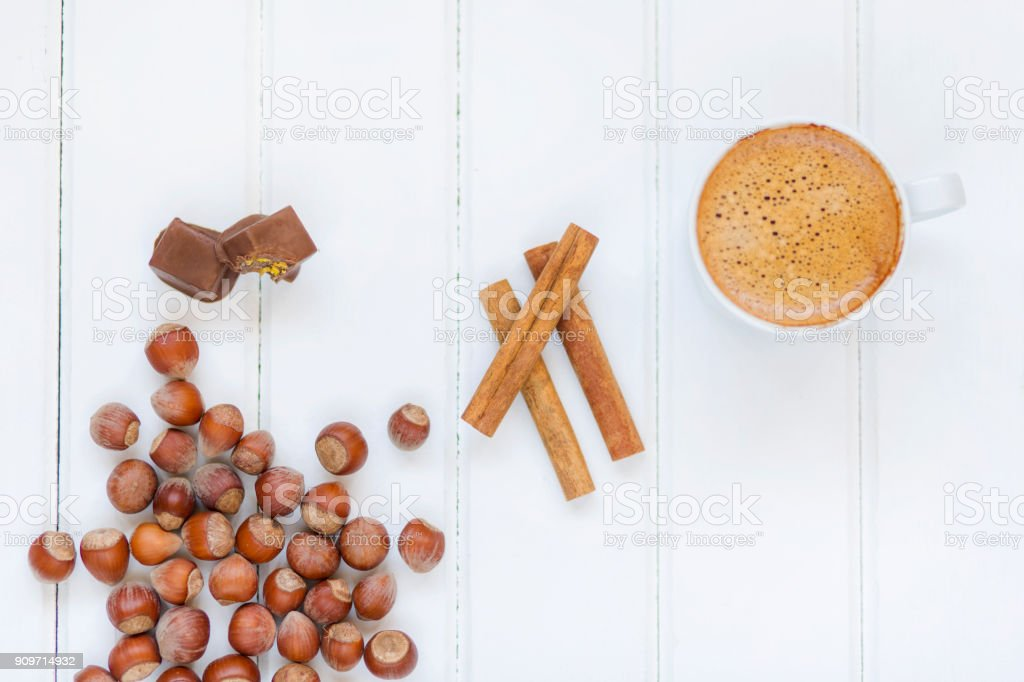 Coffee Cup,Chocolate,Nuts and cinnamon on white wood table