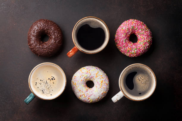 Coffee cups and colorful donuts stock photo