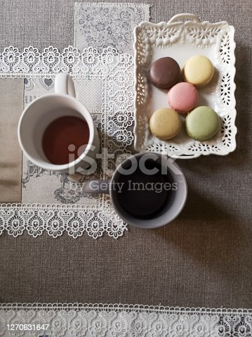 Flat lay of table with runner, coffee cups and macaroons top view