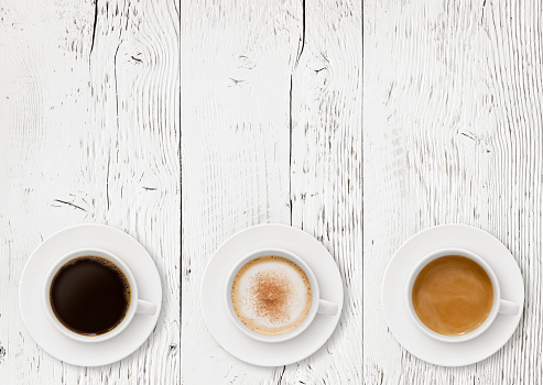 Coffee cups border on rustic wood background