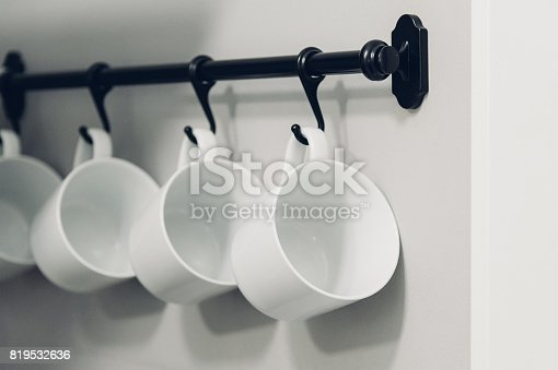 839034546istockphoto Coffee cups hanging on hooks of kitchen wall 819532636