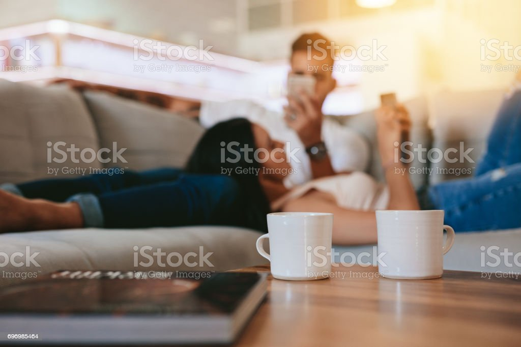 Coffee cups on table with couple relaxing in background stock photo