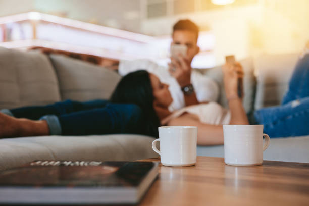 coffee cups on table with couple relaxing in background - persona in secondo piano foto e immagini stock
