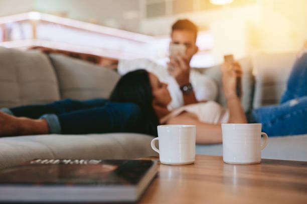 kaffeetassen auf tisch mit paar entspannende im hintergrund - tischsofa stock-fotos und bilder