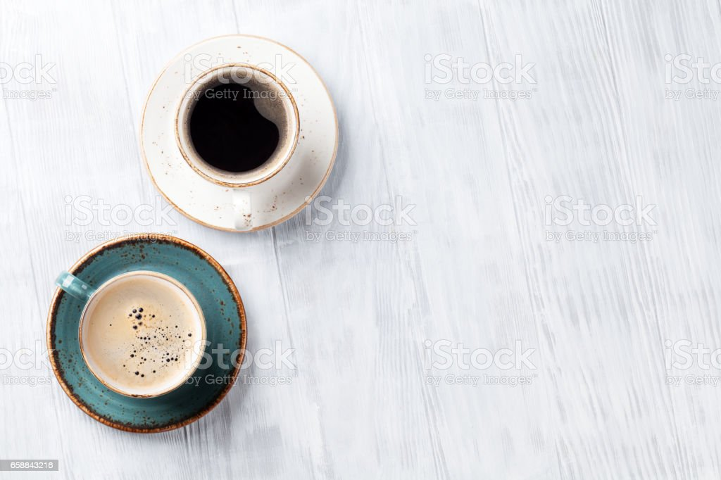 Coffee cups on wooden kitchen table stock photo
