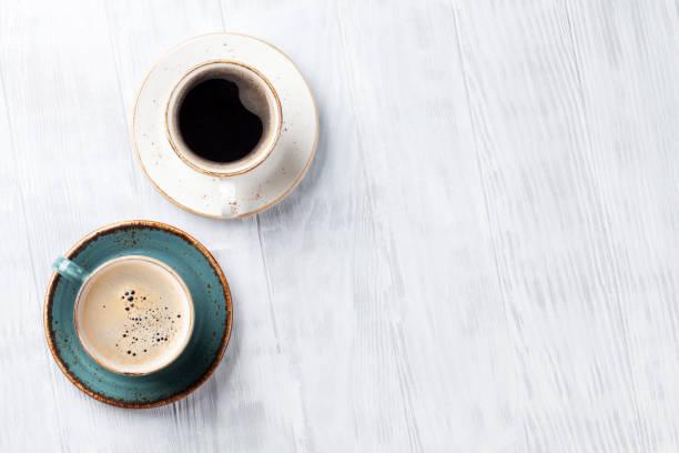copos de café na mesa da cozinha de madeira - dois objetos - fotografias e filmes do acervo