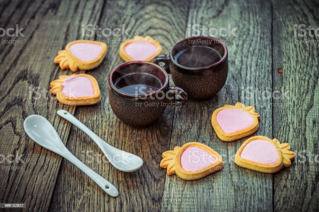 Kaffeetassen, Erdbeer Creme Kekse und weißen Löffel auf einem Holztisch - Lizenzfrei Backen Stock-Foto