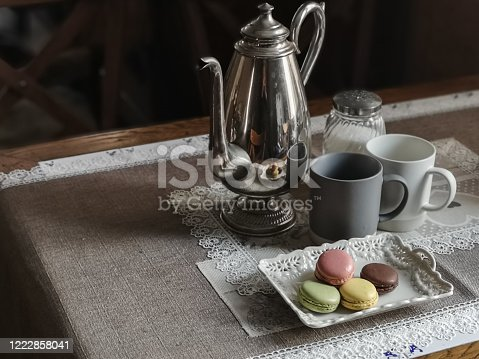Table with runner, tea pot, two coffee cups and macaroons, close-up