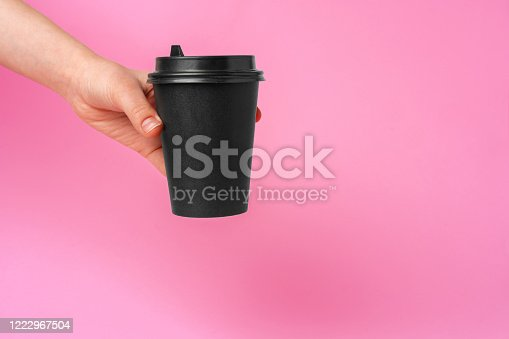 1161501551 istock photo Coffee delivery. Human hand holding takeaway coffee cup 1222967504