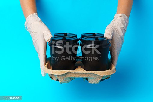 1161501551 istock photo Coffee delivery. Human hand holding takeaway coffee cup 1227533687