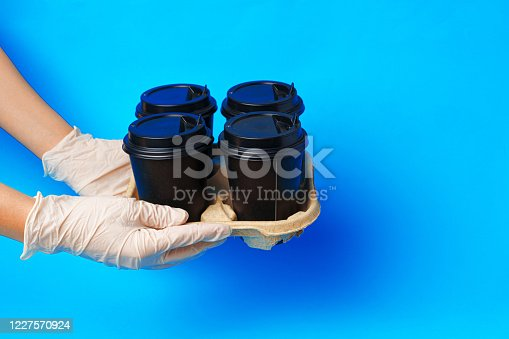 1161501551 istock photo Coffee delivery. Human hand holding takeaway coffee cup 1227570924