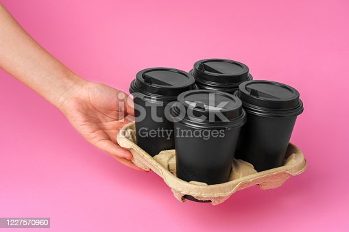 1161501551 istock photo Coffee delivery. Human hand holding takeaway coffee cup 1227570960