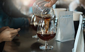 Closeup barista man pouring black coffee from glass jar into Champagne glass