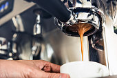 istock Coffee dripping from the machine into the cup 905029034