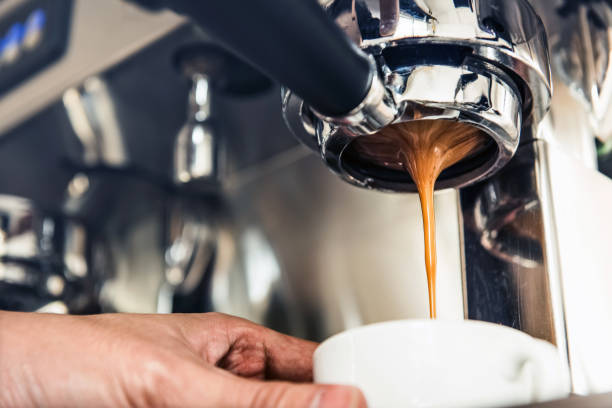 coffee dripping from the machine into the cup - barista stock photos and pictures