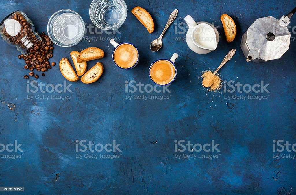 Coffee espresso, cantucci, cookies and milk over dark blue background