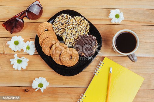 885959540 istock photo Coffee espresso stands on a wooden table with cookies, pad and pencil. 843029488