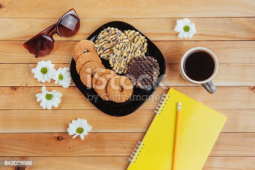 885959540 istock photo Coffee espresso stands on a wooden table with cookies, pad and pencil. 843029566